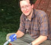 Robert Logan sits on a bench wearing blue latex gloves and holding a syringe.