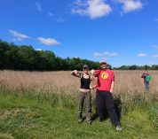Two undergraduate researchers stand at the edge of a wheat field at the Kellogg Biological Station.