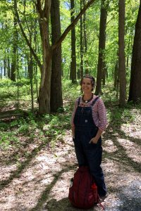 Erin Schneider stands under a canopy of trees on the Kellogg Biological Station's Farm Trail.