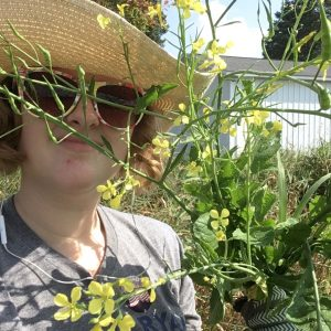 Ava Garrison poses for a photo with an uprooted weedy radish plant.