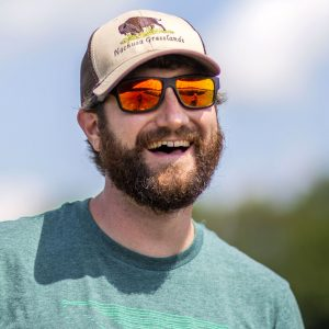 Sean Griffin, wearing sunglasses and a baseball cap, smiles for an outdoor portrait.