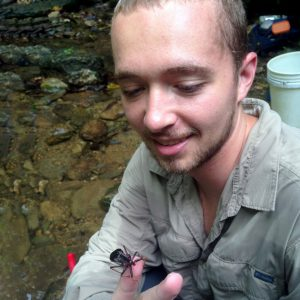 Kyle Jaynes examines a wheel bug (Arilus sp.) crawling on his finger while in Trinidad.