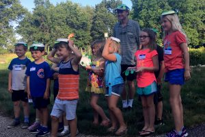 Intern Blake Hedges stands with a group of children showing off the turtle crafts they created.