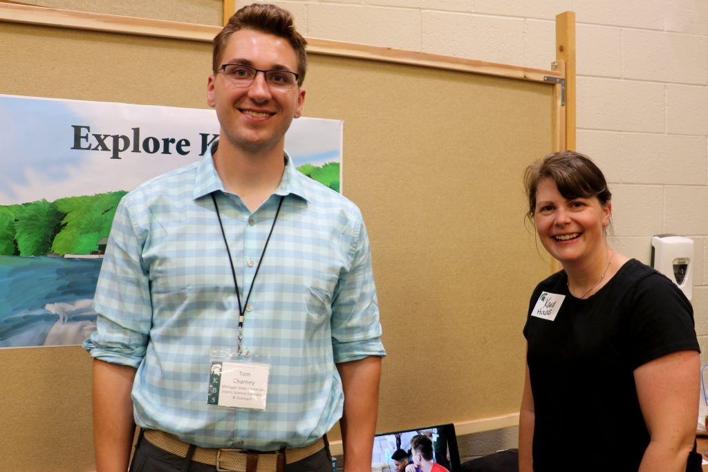 Tom  Charney stands in front of his poster project, smiling with his mentor, Kara Haas.