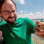 Brendan Reid poses holding three small turtles.