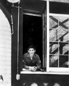 A patient at Percy Jones hospital looks out a window at the Kellogg Manor House.