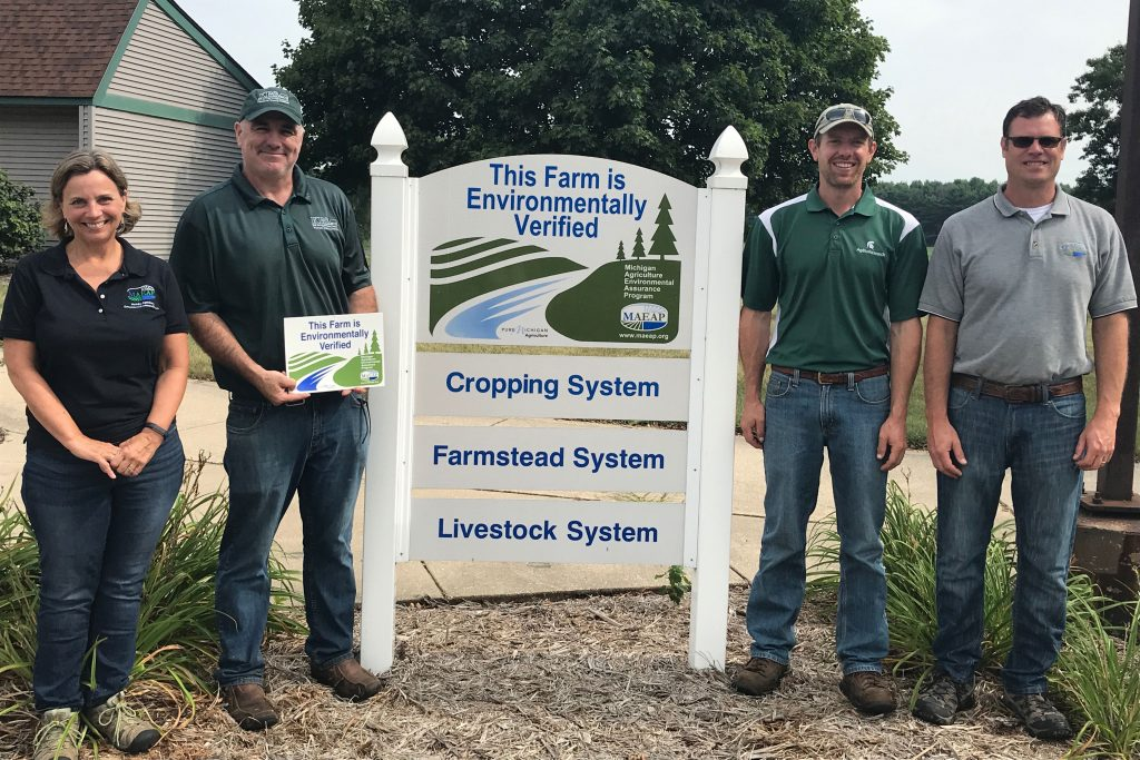Two State of Michigan agriculture and rural development staff members stand with Kellogg Farm managers Straub and Wilke around the Kellogg Farm's environmental verification sign.