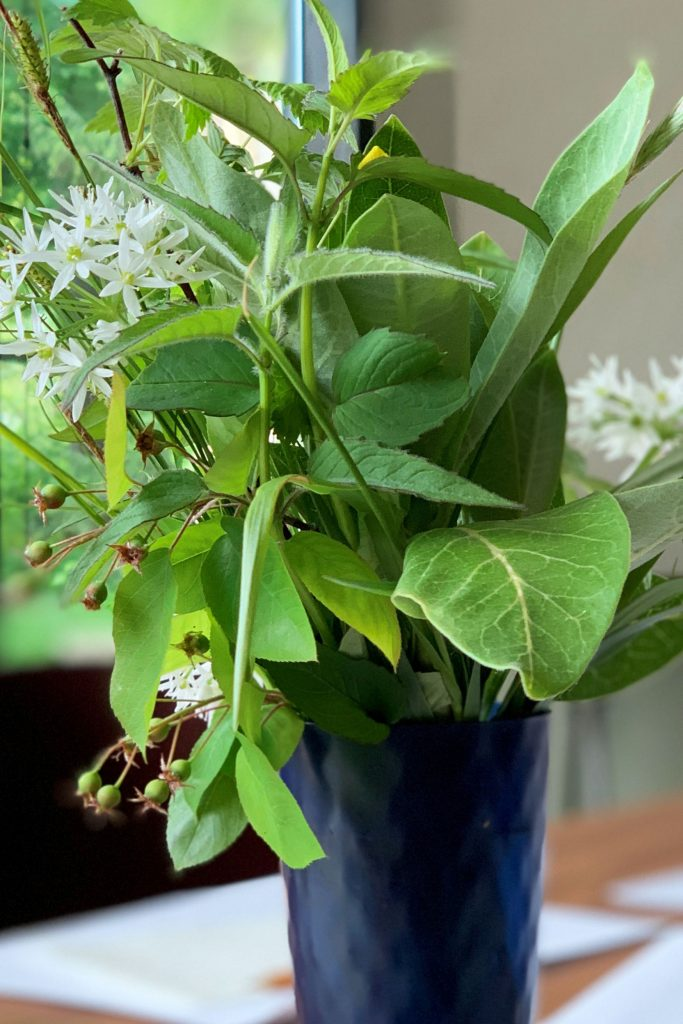 Plants including milkweed are arranged in a vase sitting on a table.