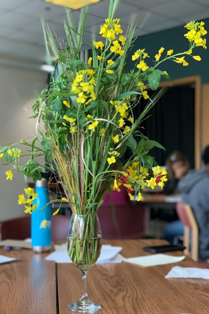 A vase filled with flowers including wheat and wood sorrel sit on a wooden table.