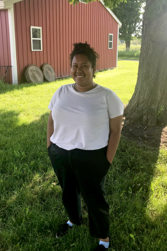 Rachel Richardson stands, smiling, in front of a tree on a summer day, wearing a white T-shirt and black pants.