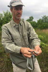 Fredric Janzen stands outdoors holding a snake.
