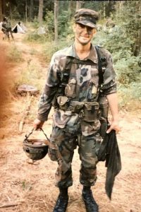 Jim Allen stands on a trail in a forested area, wearing fatigues and holding his helmet, during a deployment to Iraq.