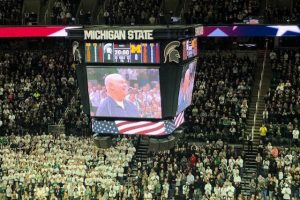 The jumbotron at MSU's Breslin Center shows a smiling Jim Allen, who was being recognized for his military service.