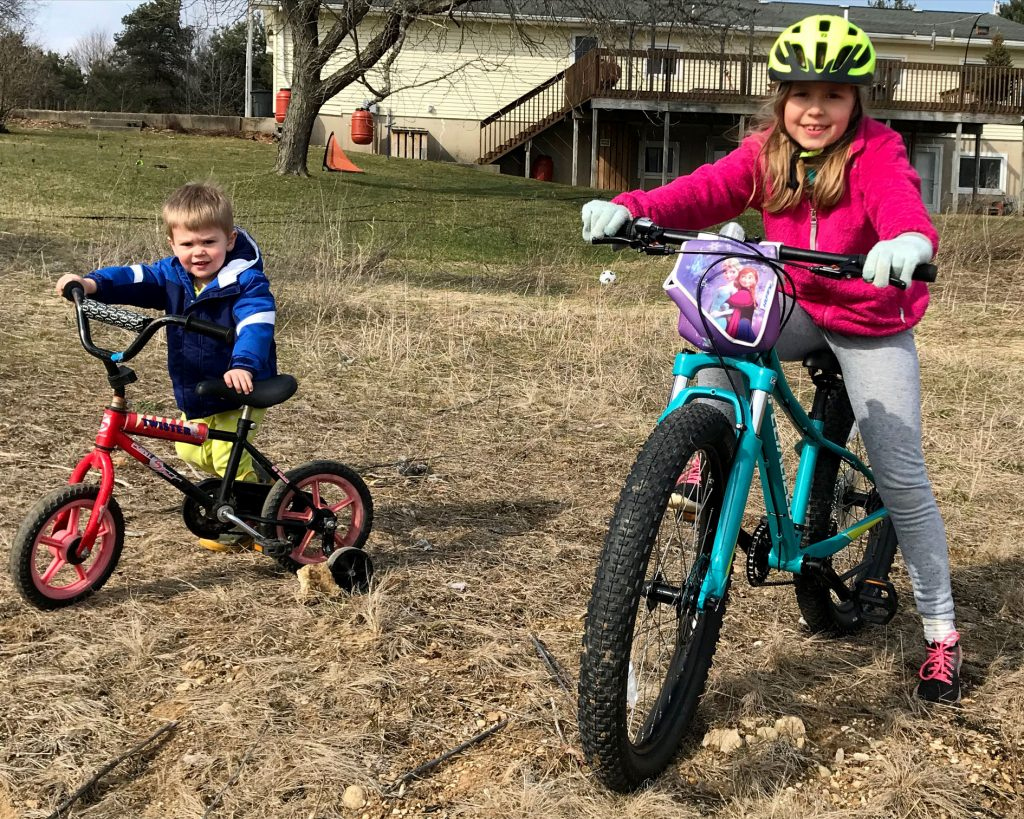 Children on bikes pose in a field in early spring.