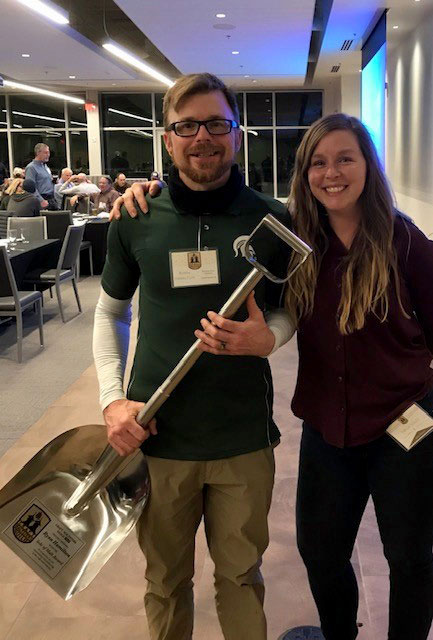 Ryan Hamilton holds a ceremonial shovel after being awarded the Sole of Malt award by Twila Soles.