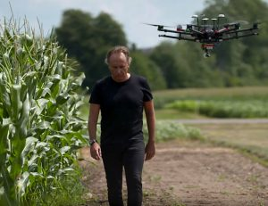 Bruno Basso walks next to a cornfield while a drone flies overhead.