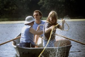 Don Hall sits in a rowboat with two colleagues, gathering samples on Wintergreen Lake.