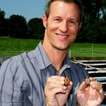 Photo of Fred Janzen holding two small turtles.