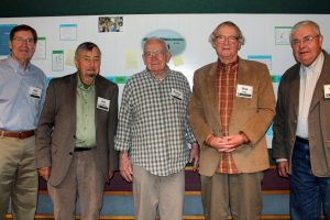 Five men stand shoulder to shoulder in from of a research poster, with Don Hall second from right.