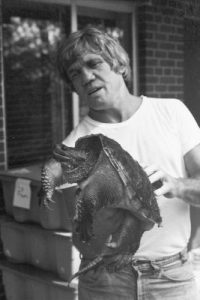 Black-and-white photo of J. Whitfield Gibbons holding a large snapping turtle.