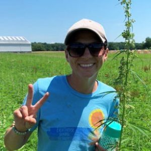 Alyssa Schuck makes a peace sign while standing in a field at Kellogg Farm.