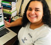 Karina Cortijo-Robles smiles while sitting at a desk with a laptop computer.