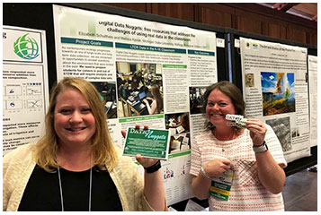 From left, Melissa Kjelvik and Elizabeth Schultheis stand in front of a poster presentation for Data Nuggets.