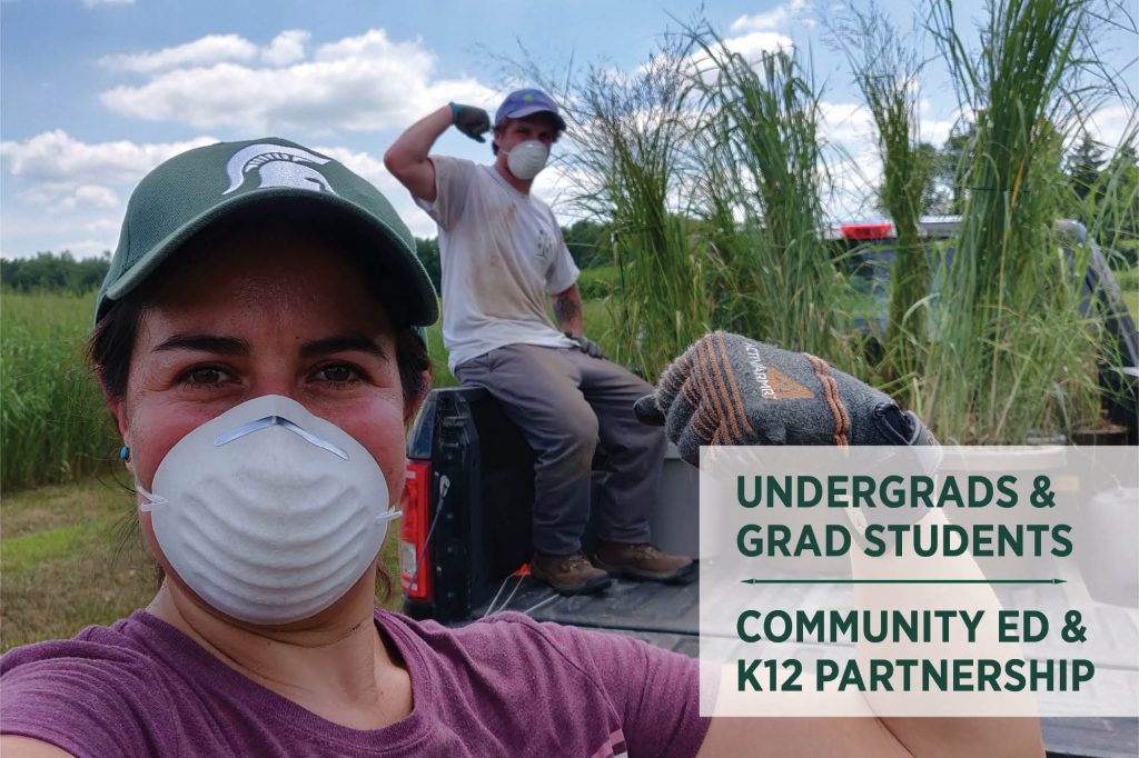 Dr. Caro Cordova and undergraduate student Colin McHugh flex arm muscles near a pickup truck bed filled with switchgrass samples.