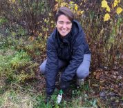 Isabela Borges crouches in a field at the KBS Long-term Ecological Research site, using a trowel to dig up plants.