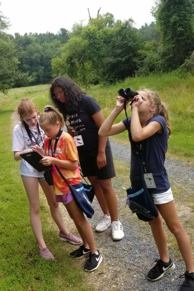 A group of children stand on the Kellogg Bird Sanctuary's Lake Loop Trail, using binoculars and a tablet computer to study birds.