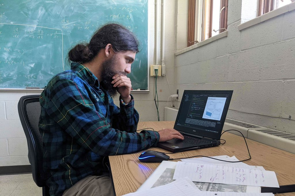 Joseph Savage sits in a classroom, focused on working on his computer. Equations are written on a chalkboard in the background.