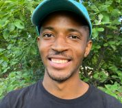 Ceco Maples, wearing a black T-shirt and a blue baseball cap, smiles at the camera against a background of trees and shrubs.