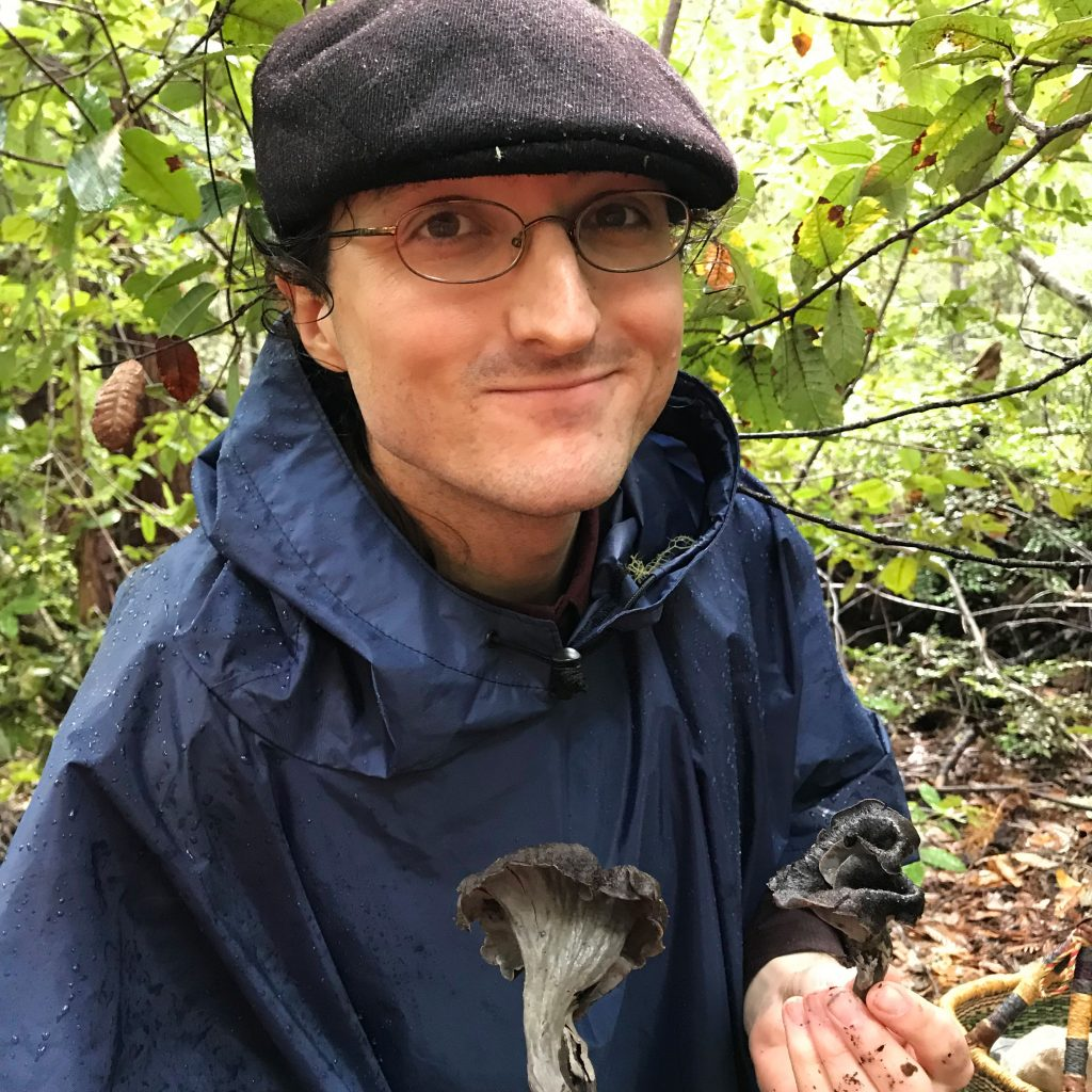 Glade Dlott stands in a wooded area wearing a jacket and hat, looking at the camera and holding two dark-colored mushrooms.