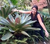 Isabela Borges poses with arms outstretched to show the size of the large plant next to her.