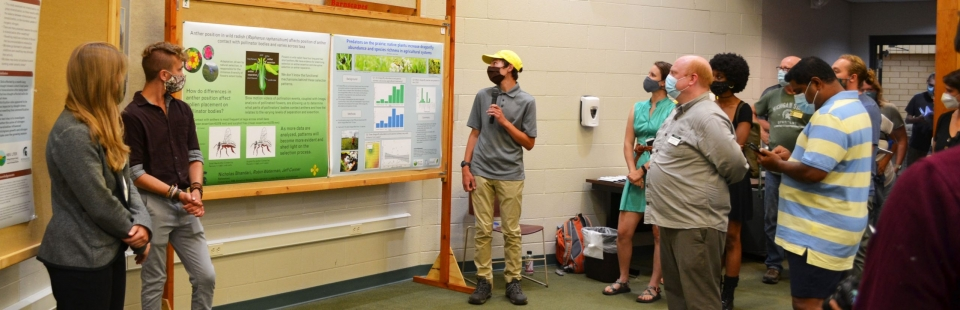 Three undergraduate college students, one holding a microphone, stand next to large research posters mounted on wooden stands. The student with the microphone speaks to a group of people standing nearby.