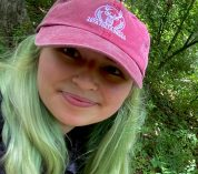 Cheyenne Cope, wearing a pink baseball cap, smiles at the camera while standing in a wooded area.