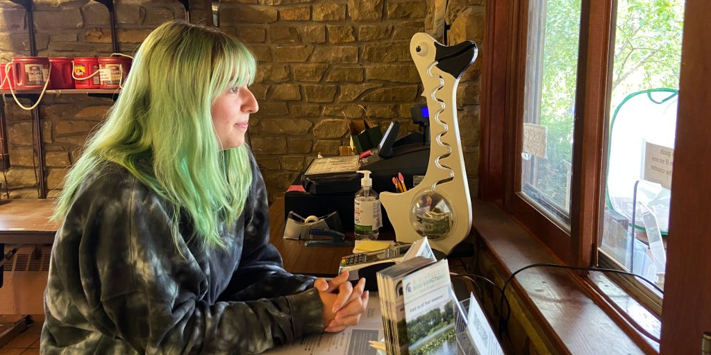 Cheyenne Cope sits at a desk inside the W.K. Kellogg Bird Sanctuary, looking out the window that visitors use to pay admission.