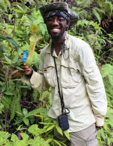 Dr. Kadeem J. Gilbert smiles while holding a Nepenthes mindanaoensis pitcher plant while in the field on Mount Hamiguitan in the Philippines.