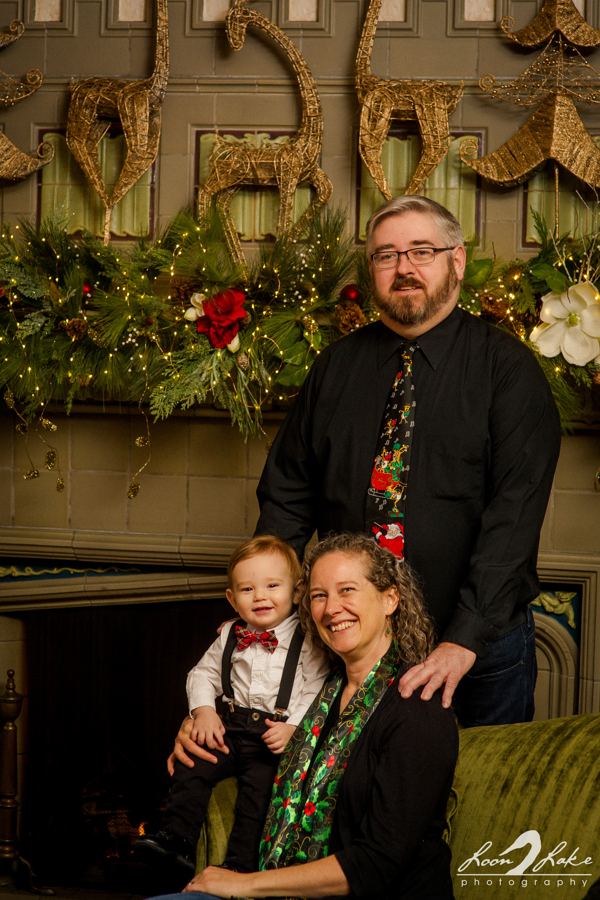 A family poses for photos inside the W.K. Kellogg Manor House in front of holiday decorations.