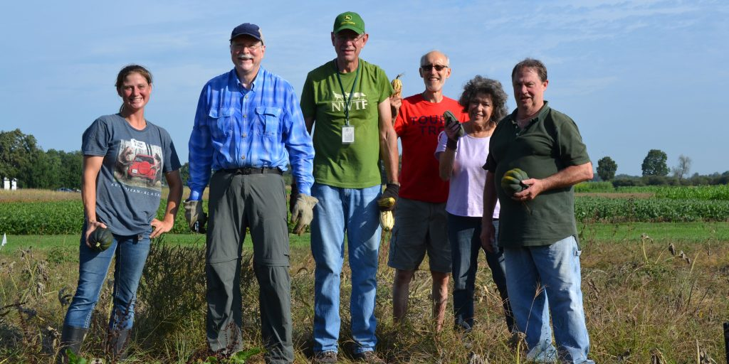 KBS volunteers stand in an agricultural field after a morning of harvesting winter squash.
